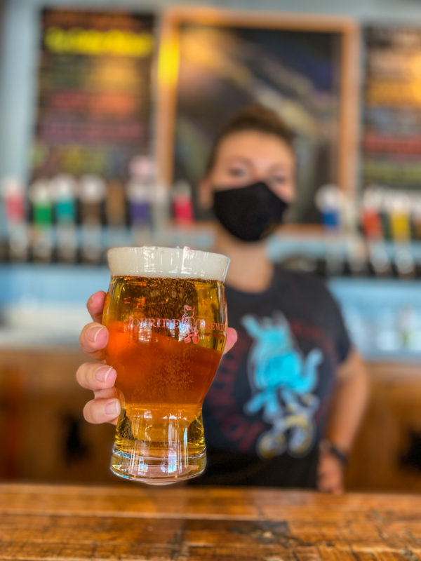 Picture of beertender holding an IPA in a glass